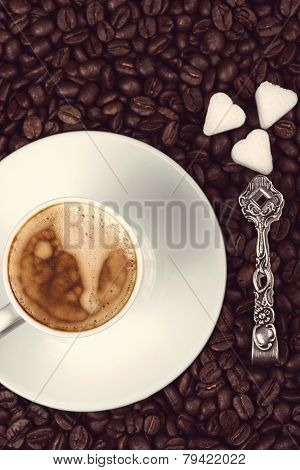 Overhead View On Cup Of Expresso Coffee  And Roasted Beans With Sugar And Silver Spoon