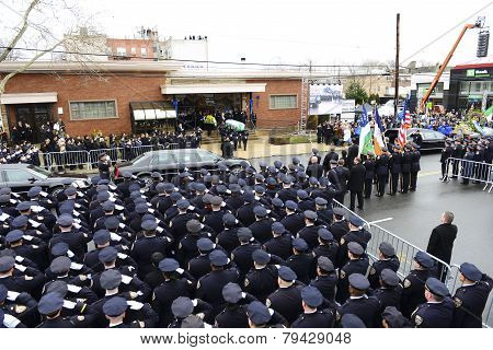 NYPD officers salute flag-draped coffin