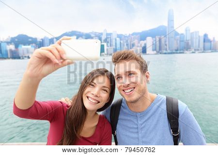Selfie - friends taking self-portrait picture photo in Hong Kong enjoying sightseeing on Tsim Sha Tsui Promenade and Avenue of Stars in Victoria Harbour, Kowloon, Hong Kong. Travel concept. poster