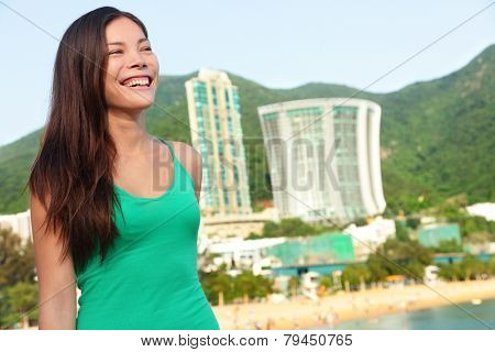 Hong Kong tourist woman at Repulse Bay beach. Beautiful Asian woman in summer dress enjoying view. Hong Kong lifestyle image.