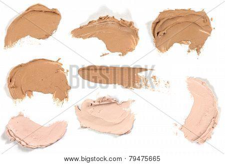 Various make up liquid powder strokes on white background