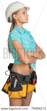 Looking up pretty girl in helmet, shorts, shirt and tool belt with tools