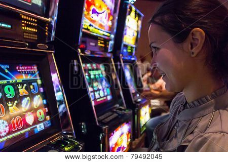 Lucky Woman Playing Slot Machines In Casino