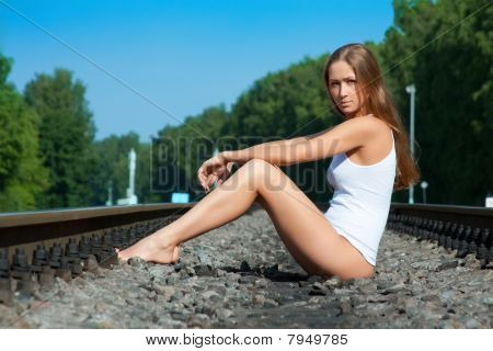 The Young Girl Sits On Railway Rails