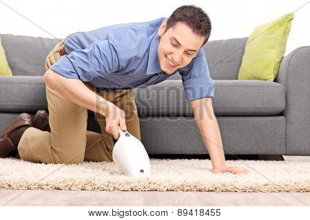 Young joyful man vacuuming a carpet with a handheld vacuum cleaner isolated on white background
