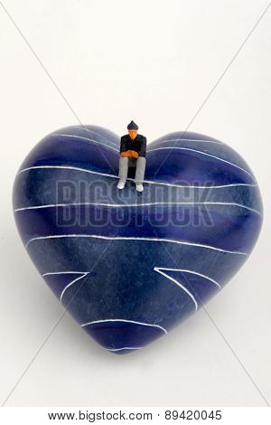 Miniature of a lonely man sitting on the top of an heart-shaped stone