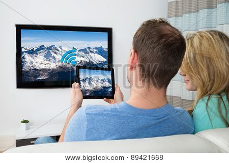 Couple With Digital Tablet And Television In Room