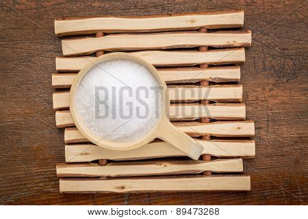 Epsom salts (Magnesium sulfate) in a rustic wooden scoop - relaxing bath concept