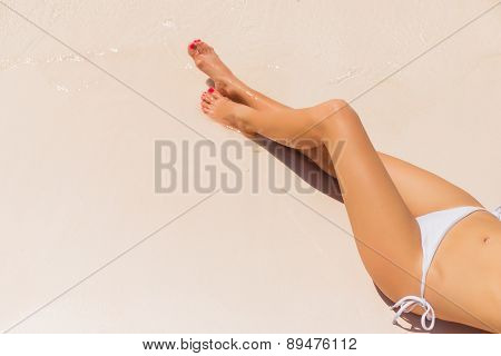 Beautiful woman's legs on the beach