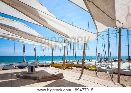 Awnings in sails shape covering relax area near sailing boats on the sandy beach in Calafell town coast of Mediterranean sea Catalonia Spain poster