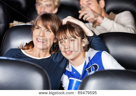 Mother and daughter watching film with family in movie theater