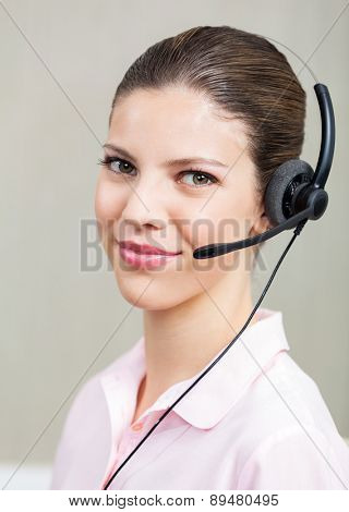 Portrait of smiling female call center employee with headphones at office