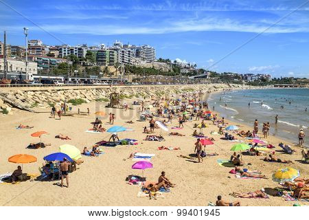 TARRAGONA, SPAIN - AUGUST 16: Sunbathers at Miracle Beach on August 16, 2015 in Tarragona, Spain. Tarragona, in the famous Costa Daurada, has several urban beaches like this, frequented by local