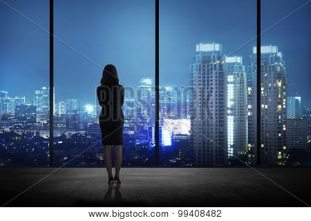 Woman Standing In His Office Looking At The City At Night