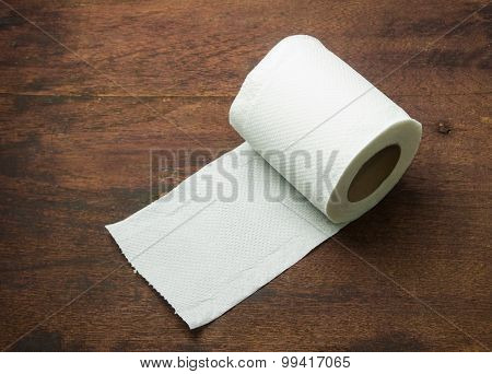 Toilet paper on wood table.