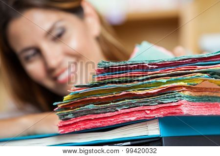 Closeup of multi colored papers with saleswoman smiling in background at shop