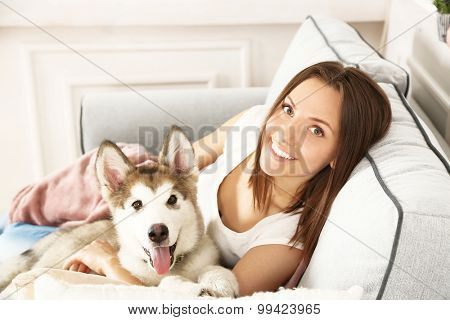 Young woman lying with malamute dog on sofa in room