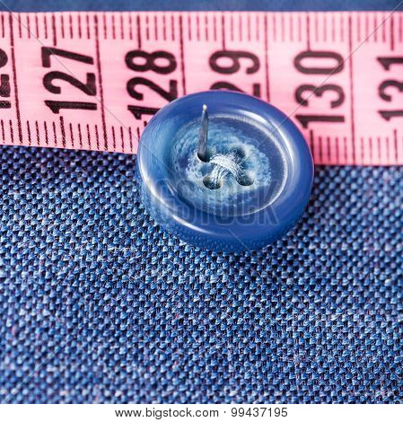 attaching of button to blue silk fabric by needle close up poster