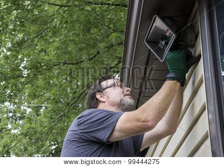 Electrician Taking Down Exterior Light