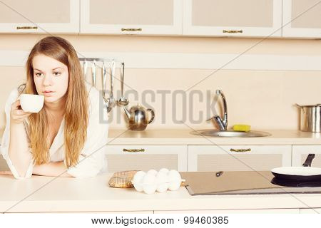 Girl  White Mens Shirt With Long Flowing Hair Is Drinking Tea. Kitchen. Morning