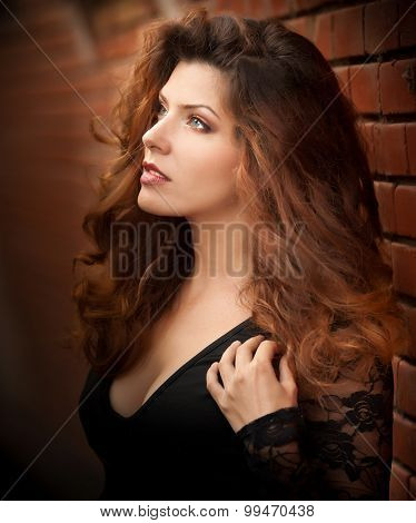 Charming young light brown hair brunette woman in black blouse near a red brick wall. Sexy gorgeous