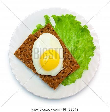 Dietetic lunch: fried eggs, lettuce, crisp bread on plate isolated over white poster