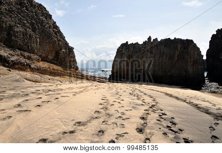 Footprints left behind on a mixed sand beach by the ocean boulders found on the islet of Djeu in Cabo Verde poster