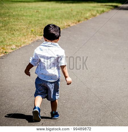 Latino child walking outside alone on a paved path in the grass poster