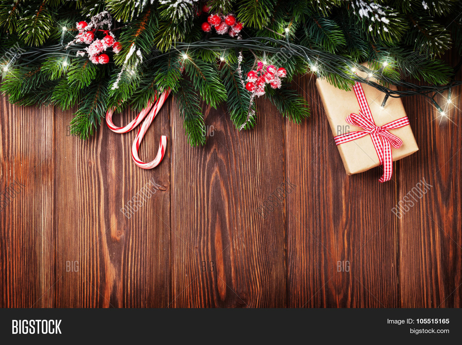 fir tree branch with christmas lights gift box and candy canes on wooden background with