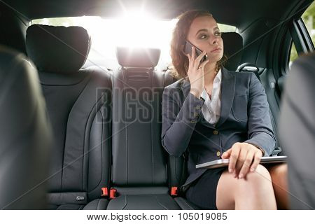 Businesswoman Making A Phone Call While Travelling To Work