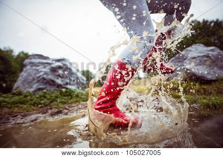 Woman splashing in muddy puddles in the countryside