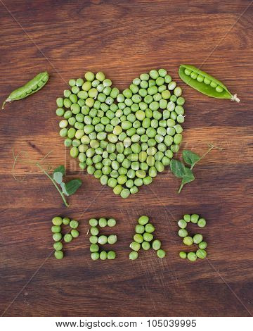 Heart made of fresh locally grown green peas on wooden background. Organic vegetable produce at a farm. Open pea pods and leaves on a side. poster
