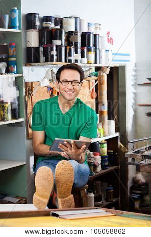 Portrait of confident worker using digital tablet while sitting in paper factory