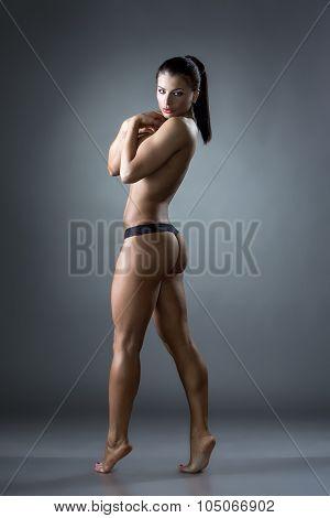 Seminude female bodybuilder posing at camera