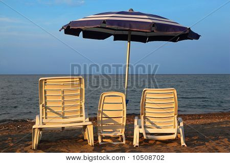 Three lounge chairs on beach