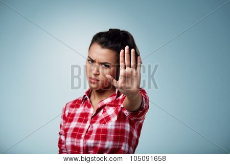 Angry Woman Gesturing Stop Sign Over Isolated Backgound. Focus On Hand.