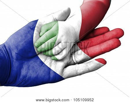 Adult Man Holding A Baby Hand With France And Italy Flags Overlaid. Isolated On White