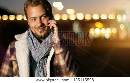 Handsome Young Man Speaking On Smart Phone At Autumn Sunset In City