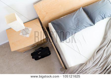 Black Bag On Floor Beside Unmade Bed In Hotel Room