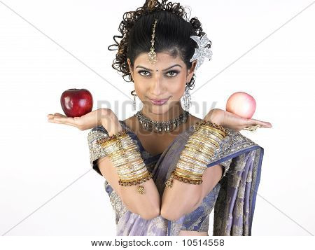 Teenage girl in rich sari holding two apples