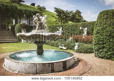 Young Sculpture And Fountain In The English Style Garden