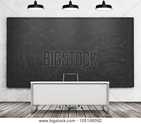 Teacher's Or Professor's Desk In A Modern University. A Huge Black Chalkboard On The Wall And Three