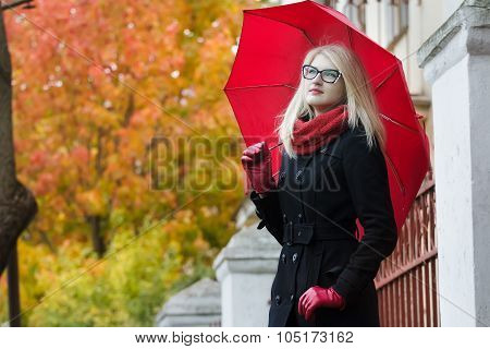 Blonde student girl with red fully collapsible umbrella and thumb in pocket posing at autumn street