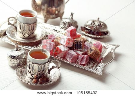 Antique tea-set with Turkish delight on table close-up poster