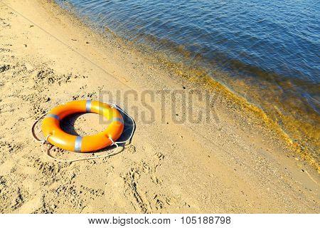 A life buoy on sandy beach
