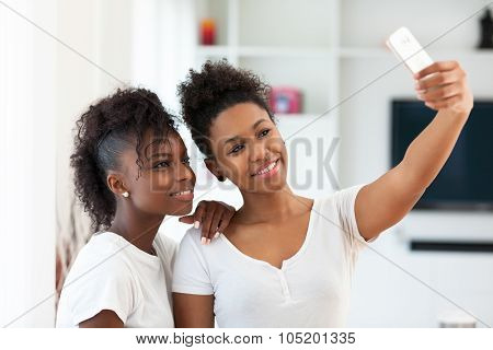 African American Teenage Girls Taking A Selfie Picture With A Smartphone