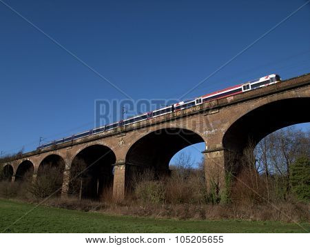 Railway Viaduct in winter with train Hanwell UK