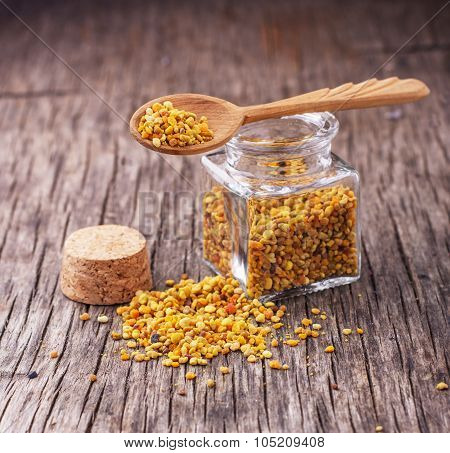 Bee pollen granules and propolis in wooden scoop