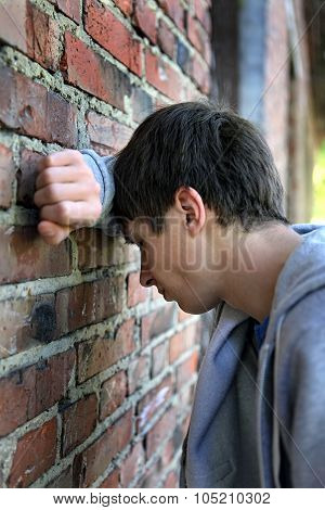Sad Young Man By The Wall