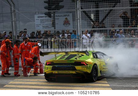 KUALA LUMPUR, MALAYSIA - AUGUST 09, 2015: Safety marshals put out the fire in the Lamborghini car driven by Byron Tong after it crashed in the race at the 2015 Kuala Lumpur City Grand Prix.
